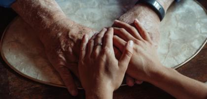 Dos manos tomadas. Un par corresponde a una persona mayor y el otro a alguien más jóven